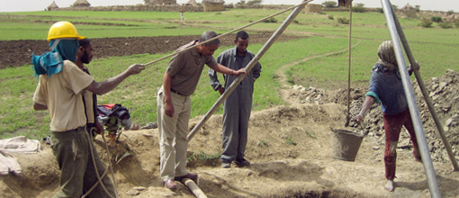 Men pulling water from a well.